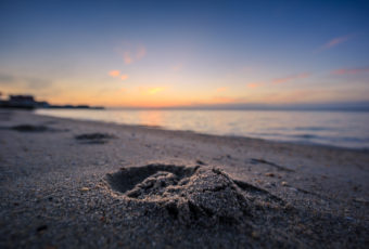 Sunset photo of a lone footprint imprinted on a bay beach.