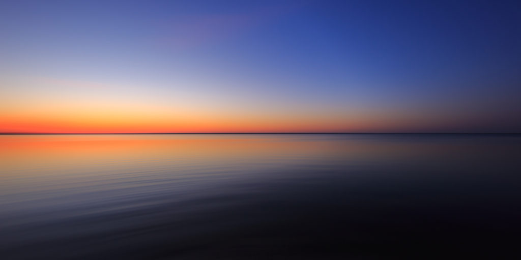 Blue hour photo with motion blur over calm bay water.