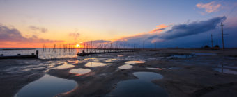 Sunset photo over reflective puddles and sand