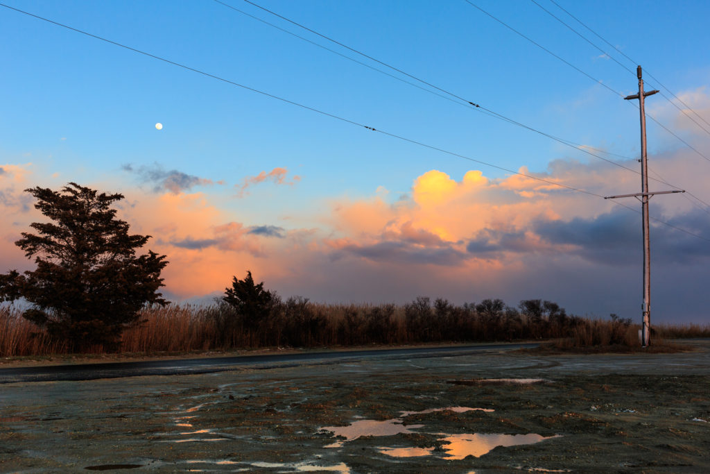 Full moon photo captured rising over pastel cumulus clouds at sunset