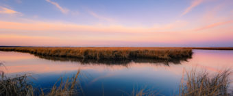 Sunset photo of pastel sky color and a watery mirror reflection.