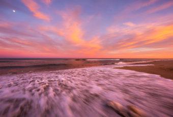 Explosive sunset photo over rushing Atlantic Ocean wash.