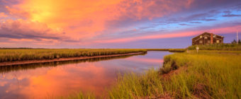 Explosive sunset photo over salt marsh, water, and house.