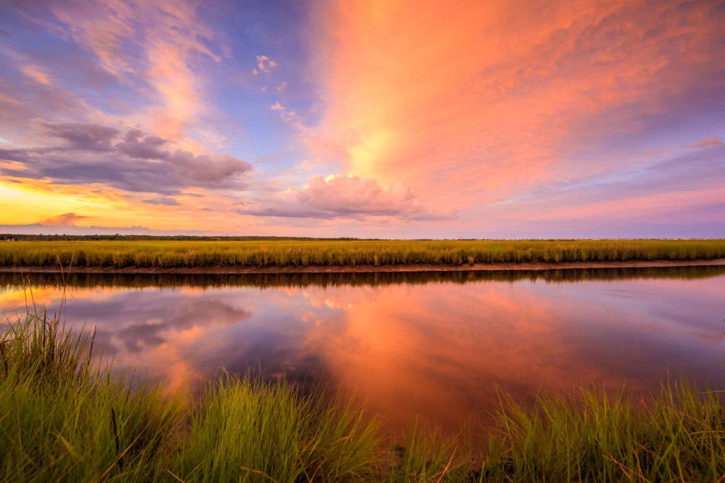 Sunset photo ignites over marsh and reflective water.