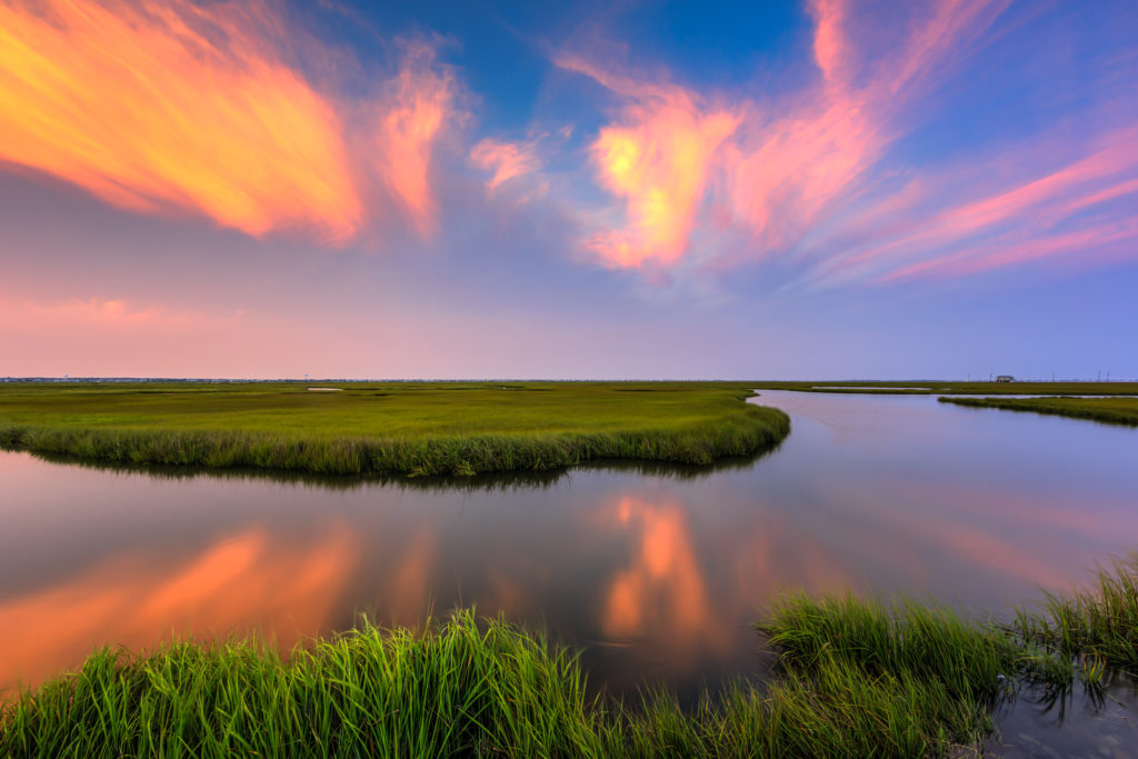 Sunset photo burns over summer salt marsh.