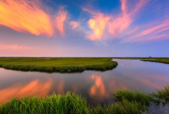 Sunset photo burns over summer salt marsh.