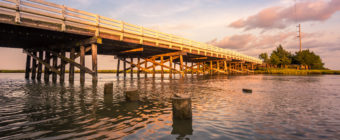 Golden hour photo of a wood bridge spanning a stretch of water.