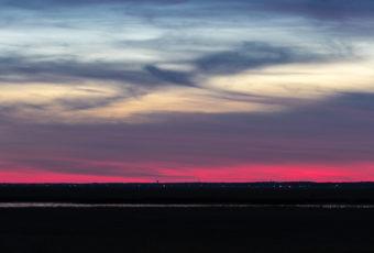 Crescent moonrise over salt marsh at blue hour.