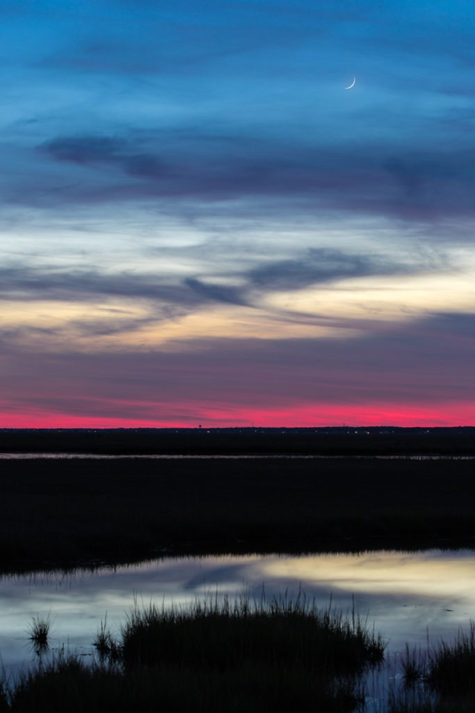 Crescent moonrise over salt marsh at blue hour.