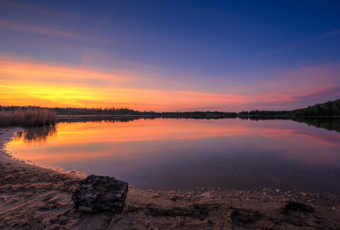 Sunset photo over sand and a calm pond.