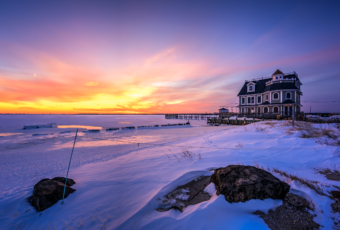 Snowy sunset photo of Antoinetta's Restaurant and a frozen bay.