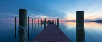 14mm blue hour photo of boat dock and calm, reflective water.