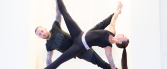 Yogis Rose Dease and Jesse Holt form an 'X' in a partner yoga pose.