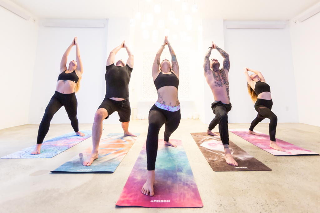 Five yogis pose in Warrior I (Virabhadrasana I) on Apeiron yoga mats at Bask Yoga.