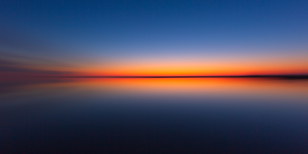 Wide angle blue hour photo over reflective bay water with motion blur.