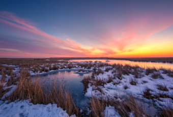14mm winter sunset photo made over frozen and snowy salt marsh.