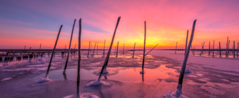 Explosive 14mm sunset photo over disused docks and frozen bay water.