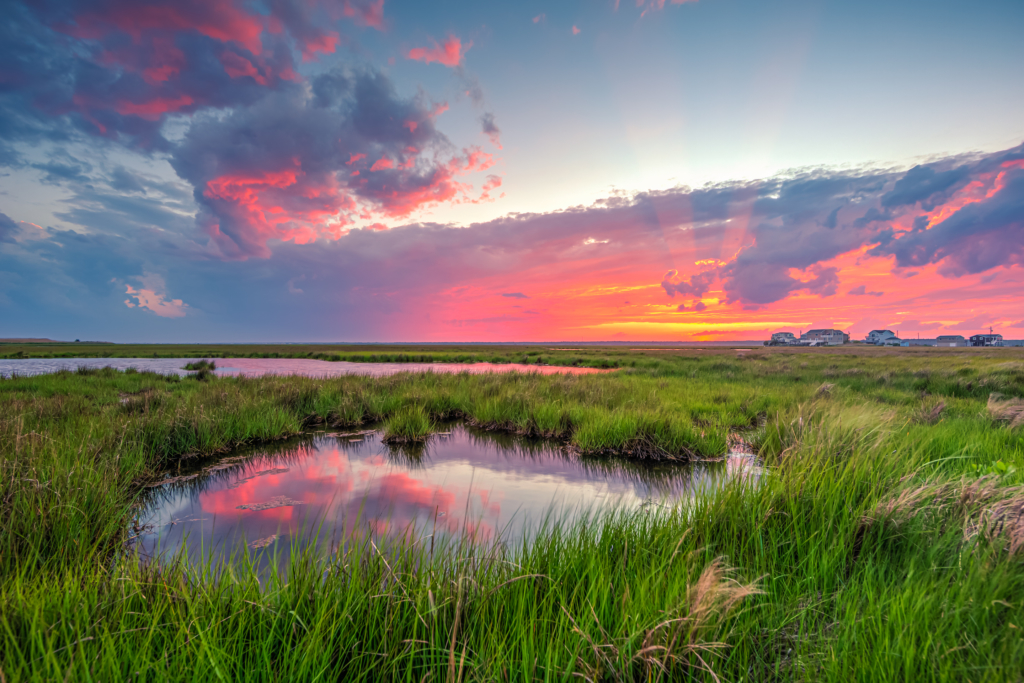 14mm wide angle HDR sunset photo featuring salt marsh, storm clouds, and anticrepuscular rays.