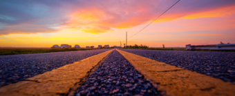 14mm wide angle sunset photo made at street level on an asphalt road surface between double yellow lines.