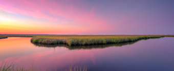 14mm wide angle sunset photo with pastel clouds and a glassy reflection on oxbow water feature at the salt marsh.