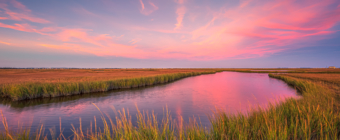 14mm wide angle sunset photo facing east over the salt marsh under pastel colored cotton candy clouds.
