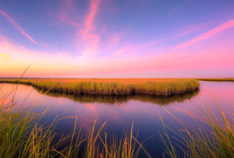 14mm wide angle sunset photo with pastel clouds, salt marsh, and calm reflective water.