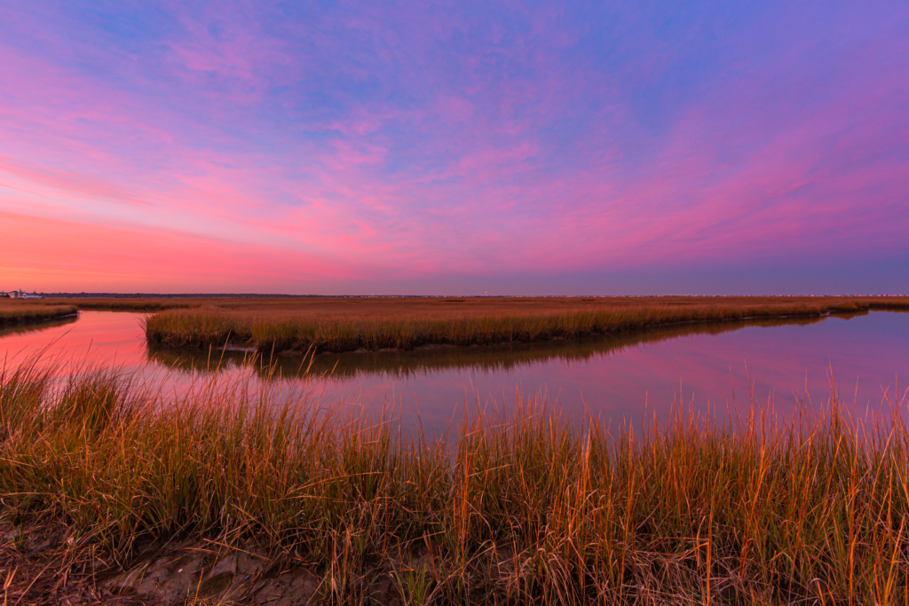 14mm wide angle sunset photo with pastel clouds reflecting in an oxbow lake in the Cedar Run Dock Road salt marsh.