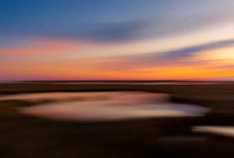 35mm sunset photo over the salt marsh using motion blur to render a brush stroke effect on the marsh and clouds.