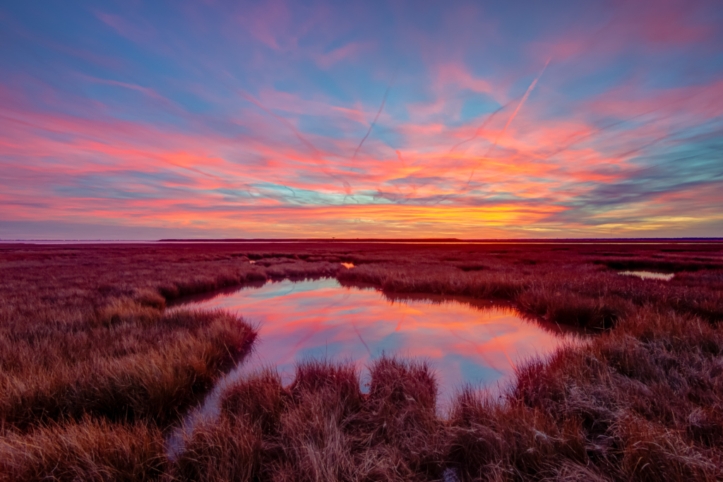 14mm wide angle sunset photo of pastel colored clouds reflected over Cedar Run Dock Road salt marsh at sundown.