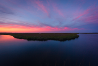 14mm wide angle landscape photo made low key at blue hour. Soft pastels color up the sky above an oxbow lake feature of the Cedar Run Dock Road salt marsh.