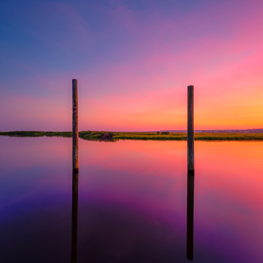 14mm square format photo of a potent pastel sunset reflecting over a glassy Cedar Run creek. Two vertical pilings mark the mid ground.