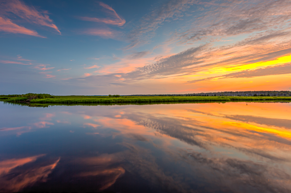 14mm wide angle sunset photograph featuring blue skies with orange, yellow, and pink pastel colored clouds reflected over mirror calm water of Cedar Run.