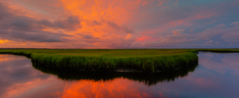 14mm wide angle sunset photo with intense pastel colored mammatus clouds smoldering over Cedar Rund Dock Road's salt marsh and still, reflective water.