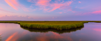 14mm wide angle photograph of an oxbow feature winding through the salt marsh. A pastel sunset sparkles in the sky, marsh grasses frame the foreground with clouds mirror reflected in the water.