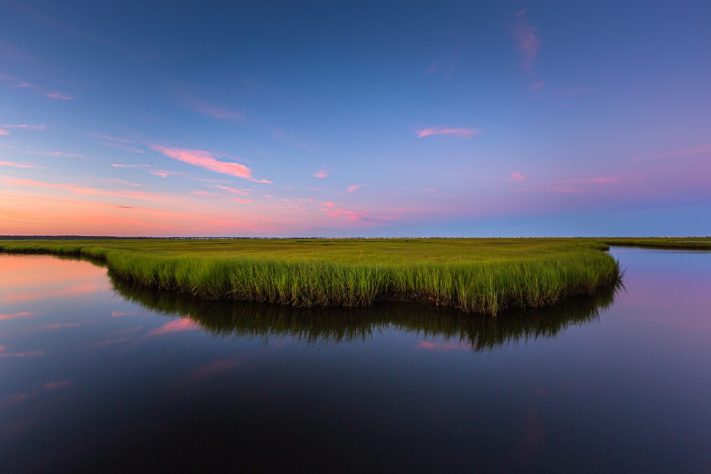 14mm wide angle photograph of a salt marsh oxbow feature at blue hour. Mirrored reflection captures the still colored pastel clouds stretched thin across the sky.