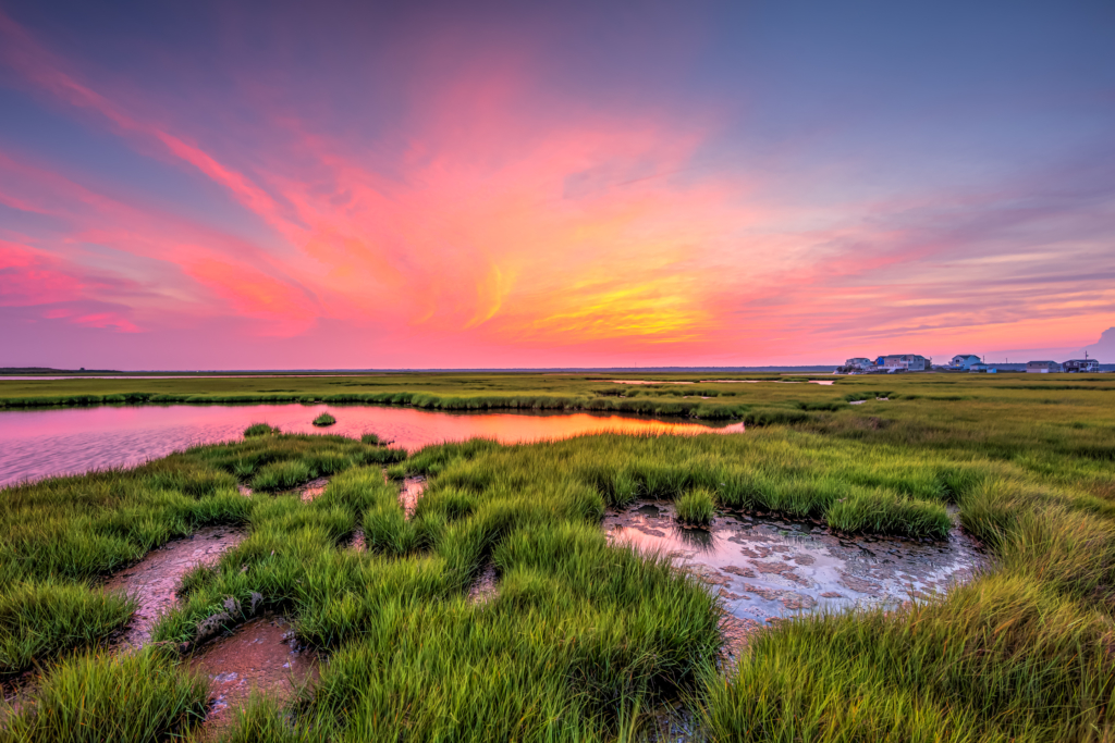 14mm wide angle photograph of a stunning sunset with pastel colored clouds sweeping across the Cedar Run Dock Road salt marsh.