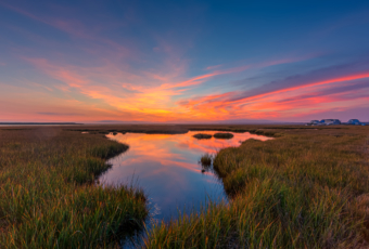 14mm wide angle photo made after sunset overlooking Cedar Run Dock Road salt marsh. Deep blues fill a sky alight with sweeping pastel clouds reflected in a marsh pool.