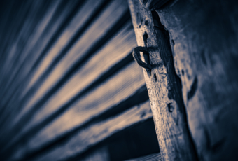 35mm sepia photograph of an old wooden structure marked by leading lines, knotted wood, and a rusted iron locking loop.