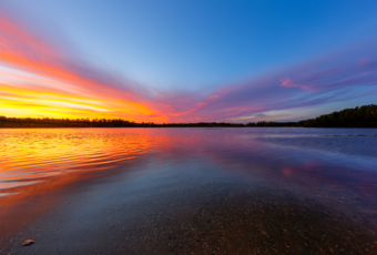 14mm wide angle sunset photo reflected over the lake at Stafford Forge Wildlife Management Area. Pastel colored clouds form an X shape pattern water reflected in symmetry as sunset gives way to blue hour.
