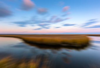 14mm blue hour photo purposefully out of focus capturing passing clouds and salt marsh with intentional camera side motion blur.