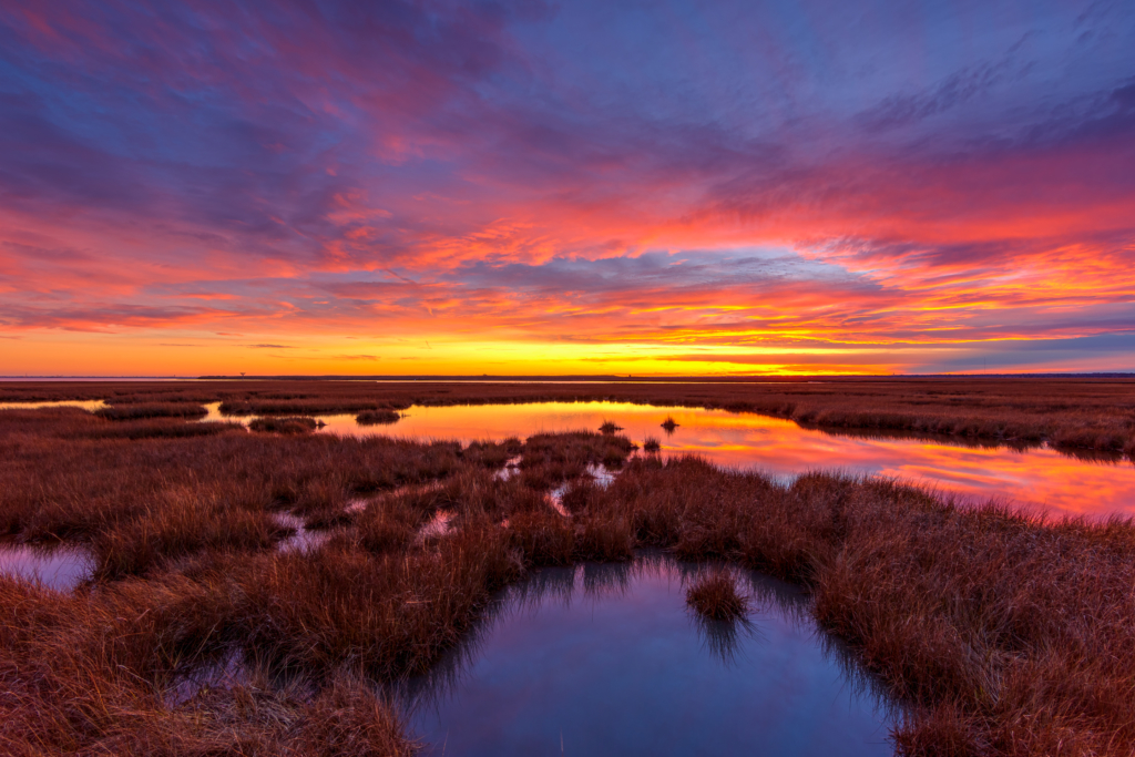 14mm wide angle HDR sunset photo of a winter sky glowing with deep pastel colored clouds reflected above Cedar Run Dock Road salt marsh.