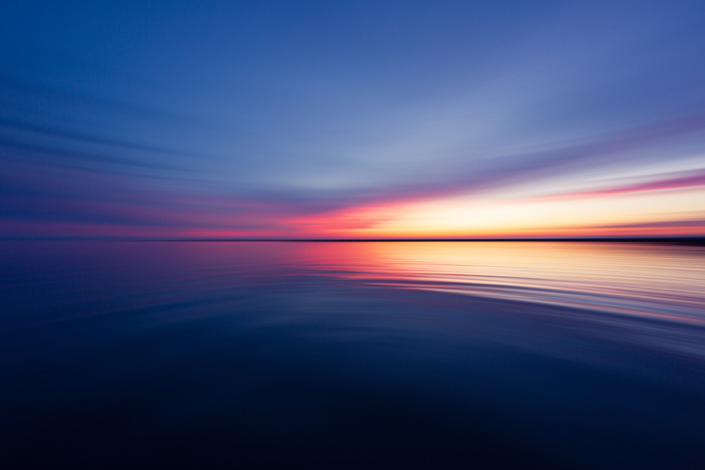 14mm wide angle landscape photo of blue hour reflected over Little Egg Harbor bay. Blended with intentional horizontal motion blur.