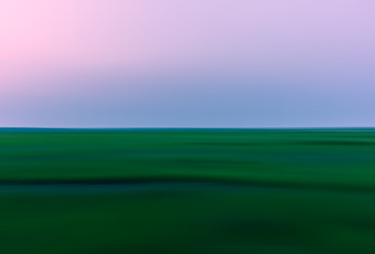 35mm photograph of green summer salt marsh at blue hour. Panning left to right creates motion blur in the landscape photograph.
