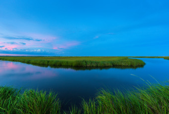 14mm wide angle photograph of an ox bow feature on Cedar Run Dock Road's salt marsh at blue hour. A hint of pink clouds twinkle in the watery reflection.