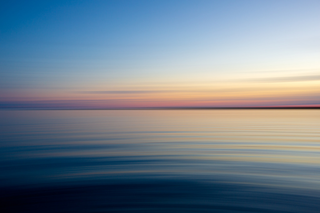 35mm blue hour photo with motion blur and slow shutter speeds bringing paint brush movement to the shimmering bay water and soothing skies.
