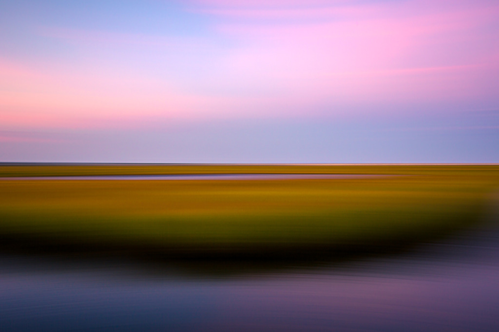 35mm panning shot photo of a New Jersey salt marsh at sunset. Late summer green marsh gives way to orange and yellow hues in a landscape picture blurred by motion.